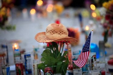 A hat is left at a makeshift memorial during a vigil to mark one week since the mass shooting at the Route 91 Harvest country music festival, on the corner of Sahara Avenue and Las Vegas Boulevard at the north end of the Las Vegas Strip; Photo by Drew Angerer/Getty Images